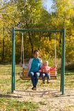 Child with mom ride on a swing in autumn royalty free stock images