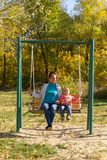 Child with mom ride on a swing in autumn royalty free stock photos