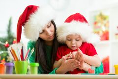 Child and mom in Santa hats making christmas tree Royalty Free Stock Photo