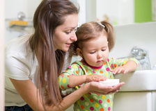 Child and mom washing hands with soap in the Royalty Free Stock Images