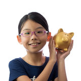 Child money savings concept. Little Asian girl holding golden piggy bank in hand with smiling face Royalty Free Stock Photo