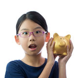 Child money savings concept. Little Asian girl holding golden piggy bank with surprise face Royalty Free Stock Photo
