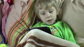 Child in a morbid state always with the tablet stock video footage