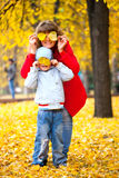 Child and mother with autumn leaves Royalty Free Stock Images