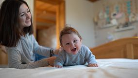 Child and mother on bed. Mom and baby boy playing in sunny bedroom. Parent and little kid relaxing at home. Family having fun stock footage