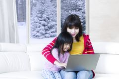 Child and mother browsing internet on laptop Royalty Free Stock Image