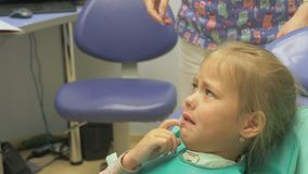 Child with a mother at a dentist`s reception. The girl lies in the chair, behind her mother. The doctor works with an
