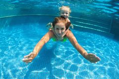 Child with mother dive underwater in swimming pool stock image