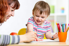 Child and mother draw with colorful pencils Stock Image