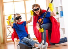Child and mother dressed as superheroes using vacuum cleaner in room. Family middle-aged woman and daughter have a fun Royalty Free Stock Photography