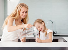 Child with mother drinking water. From glass. Happy family at home in kitchen stock image