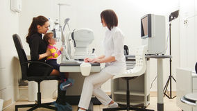 Child with Mother in eye clinic - children ophthalmology - optometrist Checks Child`s Eye Royalty Free Stock Images