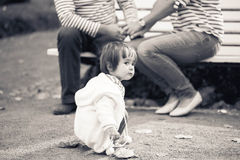 Child with mother and father in the park. Black and white. Stock Photo