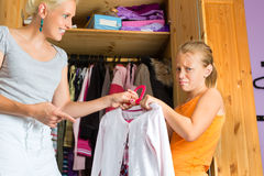 Child and mother in front of closet. Family - child and mother in front of closet or wardrobe, teenager should put on a dress but does not like it royalty free stock photography