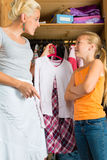 Child and mother in front of closet. Family - child and mother in front of closet or wardrobe, teenager should put on a dress but does not like it royalty free stock photos