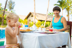 Child with mother have a breakfast. Near a swimming pool Stock Photo