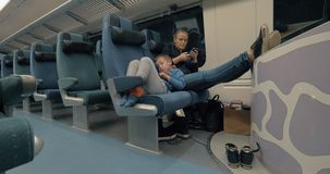 Mother and child passing the time with electronics during train journey. Child and mother having a train journey. Tired boy with digital tablet lying on the seat stock footage
