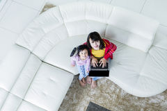 Child and mother with laptop smiling Stock Photo