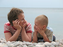 Child and mother lie on beach Stock Photography
