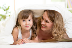 Child and mother lying under blanket in bed Royalty Free Stock Photography