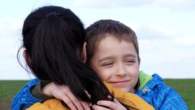 The child and the mother. Mother's Day. A happy family in the open air. Cute boy hugs his mom. Happy childhood. Portrait
