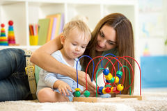 Child and mother play with educational toy Stock Photo
