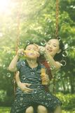 Child with mother playing soap bubbles in park. Picture of cute little boy playing soap bubbles with his mother while sitting on the swing. Shot in the park Stock Photography