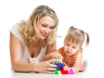 Child and mother playing together with puzzle toy Stock Images