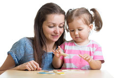Child and mother playing together with puzzle toy Stock Image