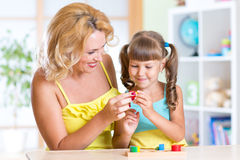 Child with mother playing together at table Stock Image