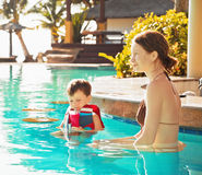 Child with mother by the pool Royalty Free Stock Photos