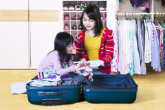 Child and mother preparing clothes. Cute little girl and her mother preparing their clothes for holiday at home Stock Photography