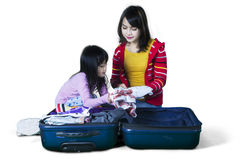Child and mother preparing clothes. Picture of a little girl and her mother preparing their clothes into a suitcase for holiday, isolated on white background Royalty Free Stock Image