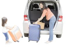Child and mother preparing for holiday. Image of cute little girl with her mother preparing suitcase into a car for holiday, isolated on white background Stock Images