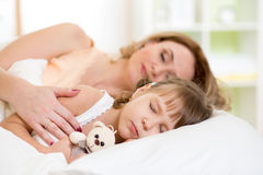 Child with mother preparing for napping on bed Stock Photos