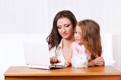 Child, mother, rabbit and laptop Stock Photos