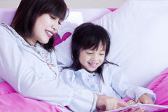 Child and mother read book on bed. Happy little girl and her mother lying on the bedroom while reading a storybook, shot at home Royalty Free Stock Image