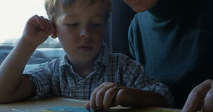 Child and mother reading childrens book in train stock footage