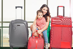 Child with mother ready to travel. Airport terminal. Travel insurance. Family carries luggage. Vacation rentals, packages. Suitcase. Tourism. Tourist bag Stock Image