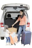 Child and mother ready for vacation. Little girl helping her mother to carrying a suitcase into a car while preparing for holiday, isolated on white background Stock Images