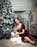 Child with mother receiving near Christmas tree. Stock Photo