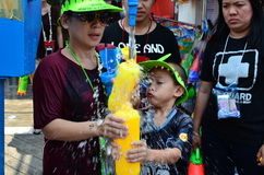 Child with mother refill water gun for celebrating Songkran festival Stock Photos