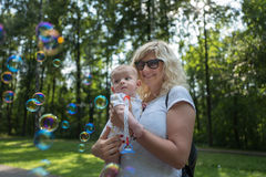 Child in mother`s arms looking to the soap bubbles. In summer urban park Royalty Free Stock Image