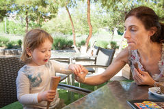 Child and mother sharing ice cream cone Stock Photo