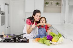 Child and mother showing thumbs up. Beautiful mother with her daughter showing thumbs up while cooking together in the kitchen Royalty Free Stock Photos
