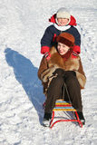 Child with mother on sled Stock Images