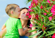 Child with mother smelling pink flowers. stock photography