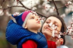 Child with mother sniffing flowers stock image