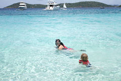 Child and mother snorkeling in tropical ocean Royalty Free Stock Images