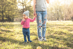 Child with mother standing together with holding hands in summer park on grass. Main subject is child. Unrecognizable mother on ph Royalty Free Stock Images